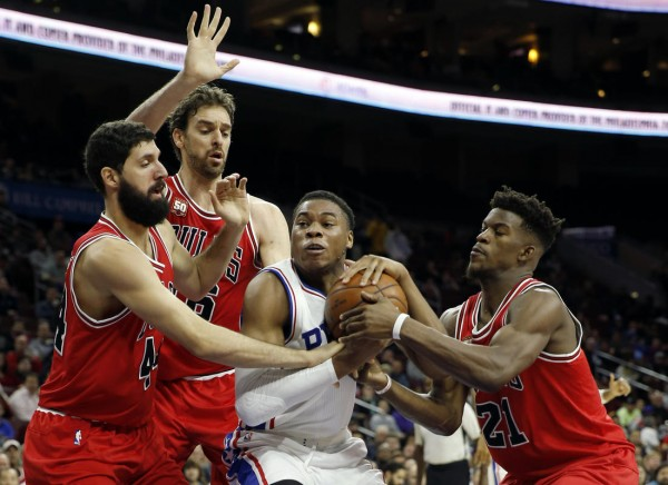 Philadelphia 76ers' Richaun Holmes, second from right, tries to hang onto the ball against Chicago Bulls' Jimmy Butler, from right, Pau Gasol and Nikola Mirotic in the first half of an NBA basketball game, Monday, Nov. 9, 2015, in Philadelphia. (AP Photo/Matt Slocum)