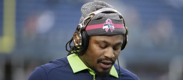 Seattle Seahawks running back Marshawn Lynch stands on the field during warmups before an NFL football game against the Detroit Lions, Monday, Oct. 5, 2015, in Seattle as he wears a hat for breast cancer awareness. Lynch was not expected to play in the game due to an injury. (AP Photo/Elaine Thompson)
